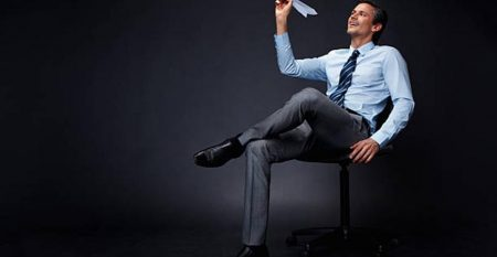 Businessman holding paper airplane